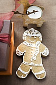 Gingerbread man beside Christmas gifts
