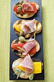 Crostini with raw ham, peppers and giant capers