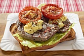 Beef steak and tomatoes on toast on paper plate