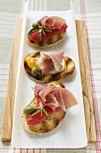 Several crostini with raw ham, peppers and giant capers
