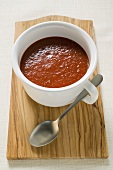 Tomato soup in cup on chopping board