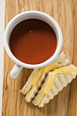 A cup of tomato soup & toasted cheese sandwiches on board