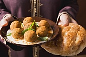 Woman serving falafel (chick-pea balls) with flatbread
