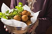 Woman serving falafel (chick-pea balls) in bowl