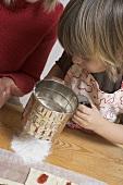 Small boy sieving flour