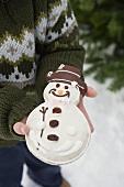 Child holding snowman biscuit