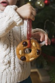Child holding gingerbread tree ornament in front of Xmas tree