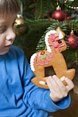 Child holding gingerbread rocking horse in front of Xmas tree