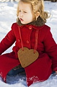 Small girl with gingerbread heart sitting in snow