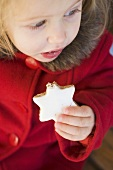 Small girl eating cinnamon star