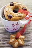 Gingerbread tree ornaments on and beside a cup