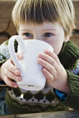 Small boy drinking hot drink in the open air