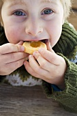 Small boy biting into a jam biscuit