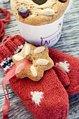 Gingerbread tree ornaments on woollen mittens and cup