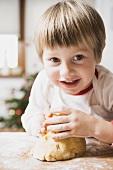 Small boy kneading dough