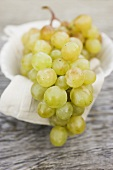 Green grapes on cloth in white bowl