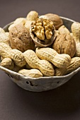 Several peanuts and walnuts in their shells