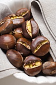 Roasted chestnuts on cloth in white bowl
