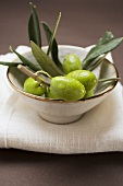 Olive sprig with green olives in bowl on linen cloth