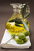 Olive sprig with green olives, carafe of olive oil behind