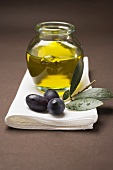 Olive sprig with black olives, jar of olive oil behind