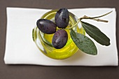 Black olives on twig on glass of olive oil