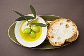 Green olives on twig in bowl of olive oil, white bread