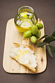 Olive sprig with green olives, white bread and olive oil
