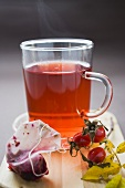 Rose hip tea in glass cup, fresh rose hips and tea bag