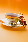Rose hip tea in china cup, fresh rose hips in saucer
