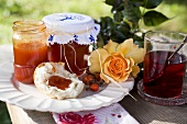 Rose hip jam in jars and on bread roll