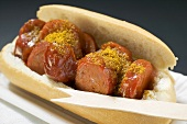Sausage with ketchup & curry powder in bread roll in paper dish