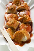 Sausage with ketchup and curry powder in paper dish