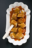 Sausage with ketchup & curry powder in paper dish (overhead)
