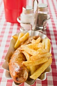 Sausage with ketchup & curry powder & chips in paper dish in restaurant