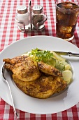 Half a roast chicken with potato salad in restaurant, cola