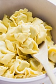 Tortellini in white bowl with wooden spoon (detail)