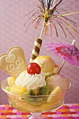 Ice cream sundae with fresh fruit and cocktail umbrella