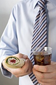 Man in tie holding wrap and cola
