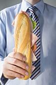 Man in tie holding ham sub sandwich