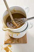 Gravy in an enamel jug with wooden spoon and whisk