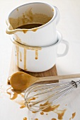 Gravy in an enamel jug, wooden spoon and whisk beside it