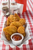 Chicken nuggets with ketchup in paper dish in snack bar