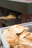 Pita bread in the oven and in a plastic crate