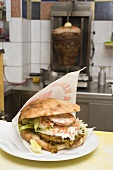 Pita bread with falafel on counter in front of döner grill