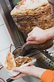 Making a döner kebab: filling pita bread with meat