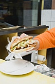 Hand putting a döner kebab on a plate in a snack bar