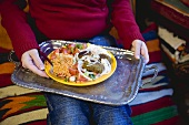 Person holding falafel with accompaniments on tray (N. Africa)