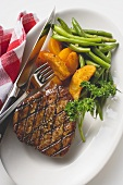 Grilled beef steak with potato wedges and green beans