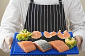 Person holding various cuts of salmon on chopping board